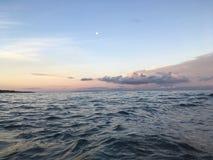 Pleine lune pendant le lever de soleil au-dessus de l'île de Niihau - vue des roches de côte de NaPali près de plage de Polihale  Photographie stock