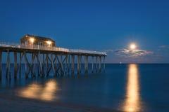 Pleine lune se levant à un pilier de pêche Photos libres de droits