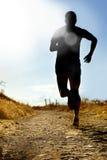 Pleine silhouette de corps de l'homme extrême de pays croisé courant sur la voie rurale pulsant au coucher du soleil Photos libres de droits
