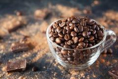 Pleine tasse en verre de grains de café Roasted sur le fond en pierre foncé avec la poudre de cacao, des morceaux de chocolat et  Image stock