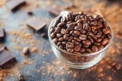Pleine tasse en verre de grains de café Roasted sur le fond en pierre foncé avec la poudre de cacao, des morceaux de chocolat et  Photographie stock libre de droits