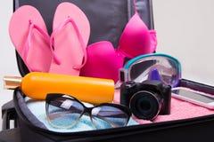 Pleine valise de voyage avec des articles d'habillement et de vacances Photo libre de droits