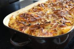 Pleines pommes de terre de rôti de cocotte en terre à l'oignon Photos stock