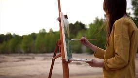 Pleinlucht het schilderen Jonge kunstenaar die aan schildersezel werken openlucht stock videobeelden