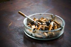 Pleins cendrier et cigarette Photographie stock libre de droits