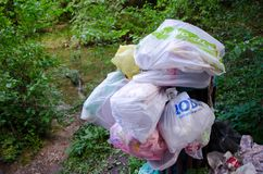 Pleins sacs des déchets en nature après le pique-nique Image stock