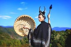 Plemienna kobieta z rogami bawić się Bawoliego bęben na górze obraz royalty free