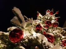 Plenerowa choinka zakrywająca w śniegu z Bożenarodzeniowym baubles i ornamentów pocztówki motywem fotografia stock