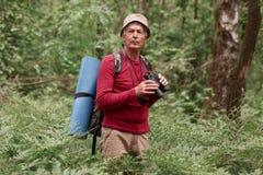 Plenerowa fotografia starszy mężczyzna z lornetkami, dywanikiem i plecakiem, stoi blisko drzew podczas gdy podróżujący w lesie, e zdjęcia royalty free