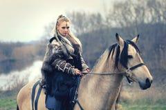 Plenerowa północna wojownik kobieta z galonowy makeup mienia ax z wilkiem obok jej gotowego atakować i osłona włosy i wojny - zdjęcie royalty free