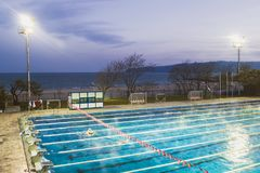 Plenerowego sporta basen zaświecał potężnymi światło reflektorów na ciemnym jesień wieczór nieba tle fotografia royalty free