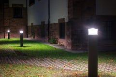 Plenerowi światła przed starym budynkiem iluminuje przejście w ogródzie przy nocą fotografia royalty free