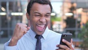 Plenerowy Afrykański biznesmen Z podnieceniem dla sukcesu na Smartphone zdjęcie wideo