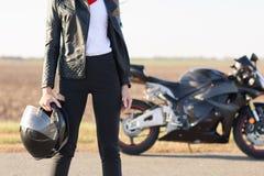 Plenerowy krótki beztwarzowy elegancki żeński rowerzysta ubierał w czerni ubraniach, trzyma hełm, pozy na drogowy pobliskim jej c fotografia stock