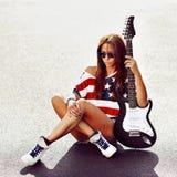 Plenerowy moda portret elegancka kobieta z gitarą elektryczną Obraz Royalty Free