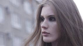 Plenerowy piękno portret młodego brązu z włosami dziewczyna patrzeje na boku nad zamazanym miasto linii tłem akcja Zamyka up dla zbiory