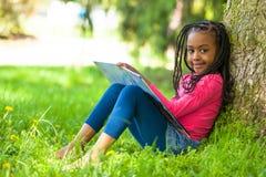 Plenerowy portret śliczna młoda czarna mała dziewczynka czyta okrzyki niezadowolenia fotografia royalty free
