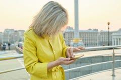 Plenerowy portret dojrza?a kobieta z smartphone, palce na ekranie sensorowym, wiadomo?? tekstowa, kopii przestrze?, z?ota godzina zdjęcie royalty free