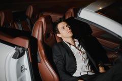 Plenerowy portret Elegancki młodego człowieka obsiadanie pozuje w jego białym kabriolecie nightlife Biznesmen w kostiumu w luksus fotografia stock