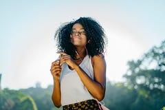 Plenerowy portret młoda piękna afrykańska dziewczyna z powabnym uśmiechem, naturalnym makijażem i długim ciemnym kędzierzawym wło Fotografia Royalty Free