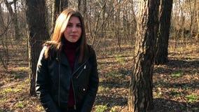 Plenerowy portret młoda piękna Kaukaska nastoletnia dziewczyna uśmiechnięta i patrzeje w kamerę, lasowa droga na wietrznym dniu zdjęcie wideo