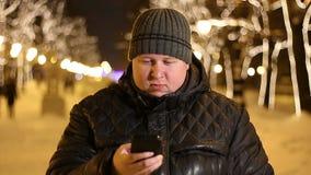Plenerowy portret młody gruby mężczyzna używa jego telefon komórkowego przy zimy nocą zdjęcie wideo