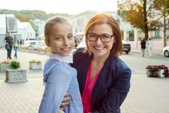 Plenerowy portret macierzysta i młoda córka, uściśnięcie, uśmiech, spojrzenie przy kamerą tła miastowy stylowy fotografia royalty free