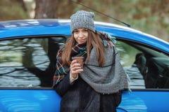 Plenerowy portret młoda caucasian kobieta, trzyma filiżankę takeaway kawa w lasu parku na zimnym sezonu dniu Ubierający w elega Zdjęcia Royalty Free