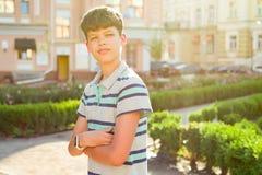 Plenerowy portret nastolatek 13, 14 lat, ch?opiec z krzy?owa? r?kami, miastowy t?o zdjęcia royalty free