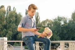 Plenerowy portret nastoletni chłopak z bukietem kwiaty, czytelniczy tekst na smartphone, miastowy tło obraz stock