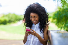 Plenerowy portret nastoletnia czarna dziewczyna używa telefon komórkowego - Zdjęcia Stock