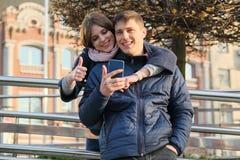 Plenerowy portret para seansu gesta znaka ok Młody człowiek i kobieta z smartphone w hełmofonach, miasta tła złota godzina zdjęcie royalty free
