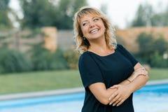 Plenerowy portret pozytywna ufna dojrzała kobieta Uśmiechnięta żeńska blondynka z rękami krzyżował, tło basen, intymny obraz royalty free