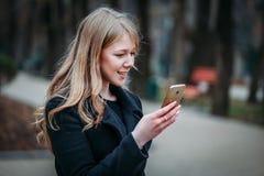 Plenerowy portret romantyczna, dosyć elegancka biznesowa długowłosa kobieta, cieszy się przespacerowanie przez miasta z telefonem fotografia stock