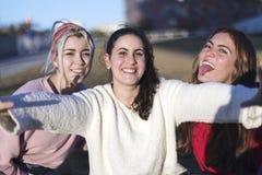 Plenerowy portret trzy przyjaciel zabawy dziewczyny bierze fotografie z smartphone przy jaskrawym zmierzchem obrazy royalty free