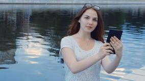 Plenerowy portret uśmiechnięta nastoletnia dziewczyna używa ekran sensorowy pastylkę zbiory wideo