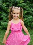 Plenerowy portret uśmiechnięty małej dziewczynki mienia kwiat Obraz Stock
