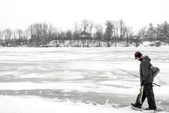 Plenerowy rybaka odprowadzenie przez zamarzniętego jezioro w zimy carryin Zdjęcie Stock