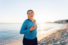Plenerowy sport, sprawność fizyczna gadżet i ludzie pojęć, - Uśmiechnięty żeński sprawności fizycznej mienia smartphone z słuchaw Fotografia Stock