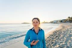Plenerowy sport, sprawność fizyczna gadżet i ludzie pojęć, - Uśmiechnięty żeński sprawności fizycznej mienia smartphone z słuchaw Obrazy Royalty Free
