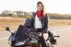 Plenerowy strzał ładny kobieta rowerzysta jest ubranym czerwonego banadana i leahter kurtka, trzyma hełm, siedzi przy szybkim cza obraz royalty free