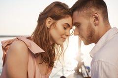Plenerowy strzał śliczna para w miłości, zamykający oczy i macanie z czołami podczas gdy żeglujący na jachcie, mieć wakacje obrazy stock
