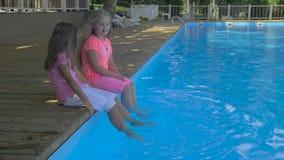 Plenerowy strzał dwa małej dziewczynki zamacza ich cieki w basenie Śliczne małe dziewczynki siedzi na krawędzi dopłynięcia zbiory wideo