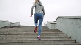 Plenerowy strzał dysponowany młoda kobieta bieg na krokach Biegacz ćwiczy na schodkach w ranku zbiory