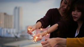 Plenerowy strzał młodzi ludzie przy dachu przyjęciem Szczęśliwa grupa Asia dziewczyny przyjaciele cieszy się sparkler i bawić się zbiory wideo