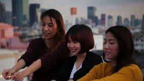 Plenerowy strzał młodzi ludzie przy dachu przyjęciem Szczęśliwa grupa Asia dziewczyny przyjaciele cieszy się sparkler i bawić się zbiory