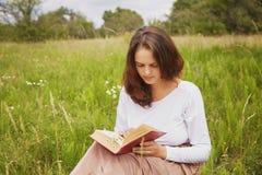 Plenerowy strzał poważna urocza młoda kobieta cieszy się lato pogodę, siedzi na zieleni polu, czyta ciekawą książkę z wielkim int zdjęcie stock