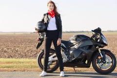 Plenerowy stylu życia pojęcie Jaźń ufny żeński rowerzysta ubierał w czerni ubraniach i czerwone bandany na szyi, trzymają hełm, p zdjęcie stock