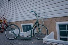 Plenerowy widok Amish rolownik jechać na rowerze lub hulajnoga opierają przeciw domowi zdjęcie royalty free