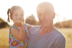 Plenerowy widok starsza samiec trzyma małego dziecka na rękach Urocza wnuczka z jej dziadek przespacerowaniem na łące wpólnie, sp zdjęcie stock